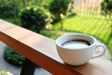 Coffee cup on wooden background in the garden