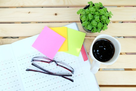 teaching stations: planner book and office tools on the wood table with black coffee