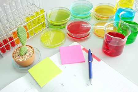 microbial: note book on laboratory table with Colorful fluid in glass ware