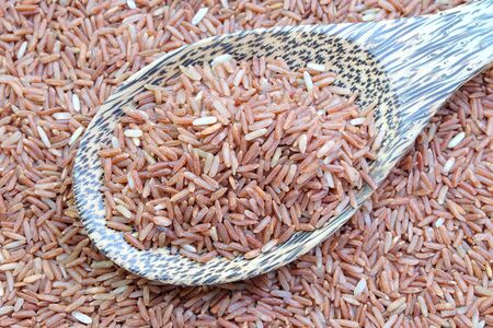 red rice in wooden spoon