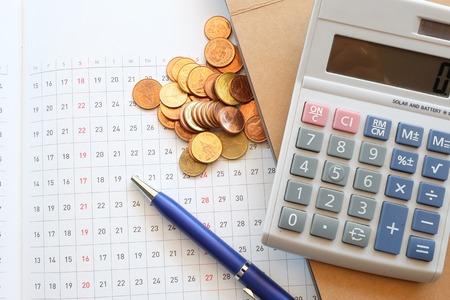 financial success: calculator and planner on wooden table with coin