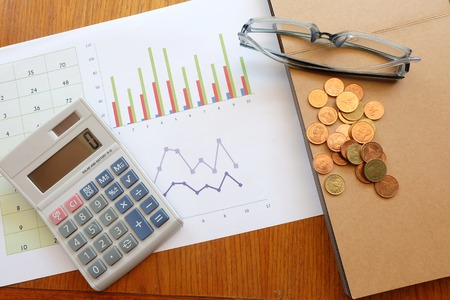 financial planning: chart and calculator on wooden table with coin