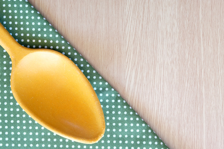 receptacle: wooden spoon on wooden and dot cloth background Stock Photo