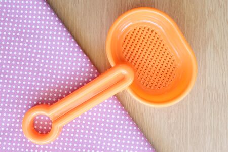 antique dishes: plastic spoon on wooden and dot cloth background