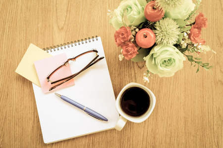 note book and chart on wooden table with vintage style