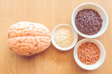 brain and three types of rice on wooden background with vintage color Stock Photo