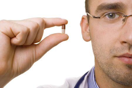 young male doctor holding pill in fingers