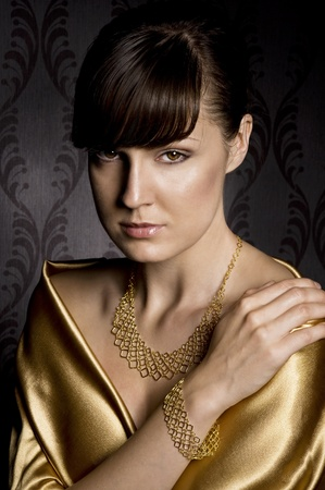 body jewelry: portrait of elegant woman wearing golden necklace and bracelet, over wallpaper background Stock Photo