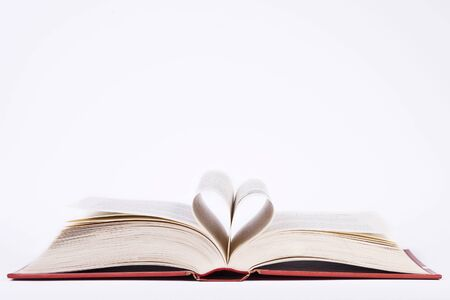 book with heart shaped pages over white background