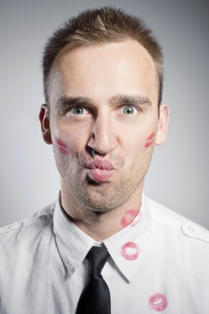 lipstick kiss: handsome young man with kisses on the chick and shirt