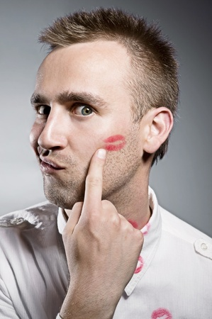 young man pointing on cheek with kiss imprint photo
