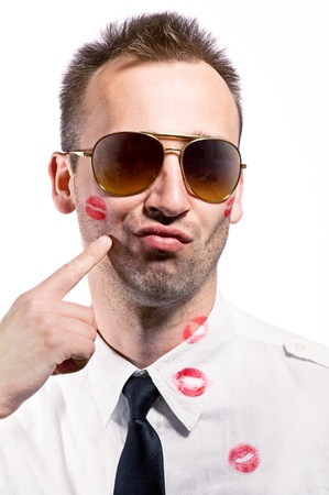 finger proof: young man pointing on cheek with lips imprint