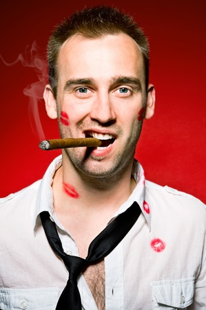young confident man with cigaro and lips imprints