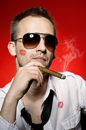 young handsome man with lips imprint smoking cigaro photo