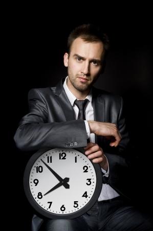punctual: empresario joven y guapo sosteniendo un reloj grande