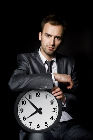 rushing hour: young handsome businessman holding big clock