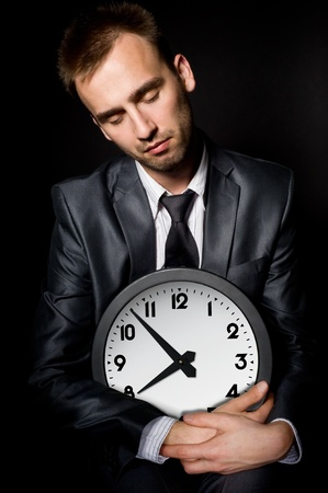 career timing: tired sleeping businessman holding clock, over black Stock Photo