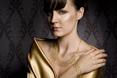portrait of elegant woman wearing golden necklace and bracelet, over wallpaper background Standard-Bild