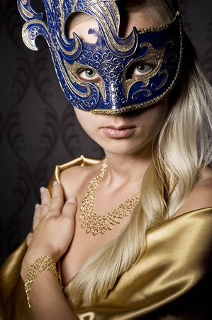 body jewelry: attractive woman wearing mask, over wallpaper background Stock Photo