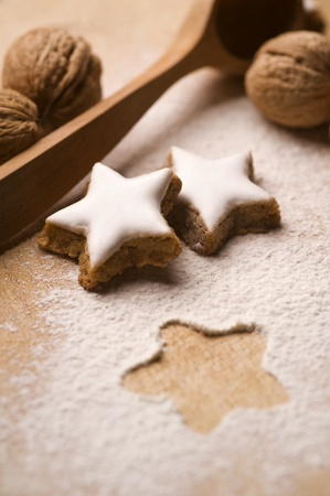 star shaped: nuts and star shaped glazed cookies on wooden board Stock Photo