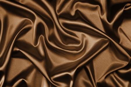 textile brown silk background draped in waves Standard-Bild