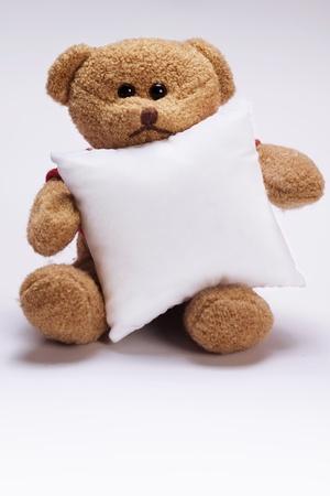 sitting plush teddy bear holding white pillow Standard-Bild