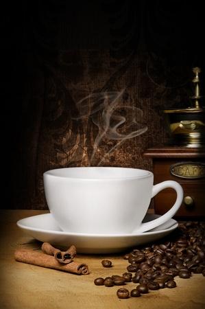winnower: hot cup of coffee, winnower, grains and aromatic cinnamon Stock Photo
