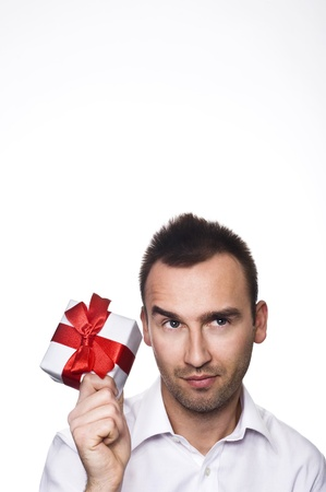 young handsome man holding a gift, over white background Standard-Bild