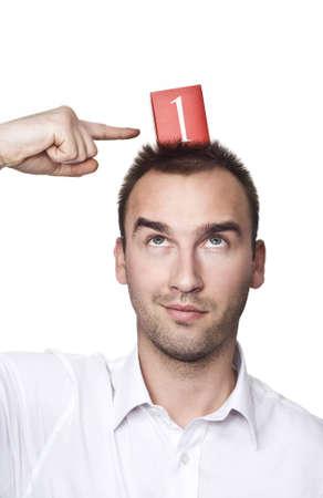 primer lugar: macho joven mirando hacia arriba y señalando con el dedo en el número uno