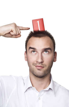 first place: young male looking up and pointing his finger at number one Stock Photo