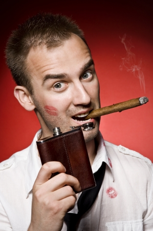 young confident man with hip flask and cigar