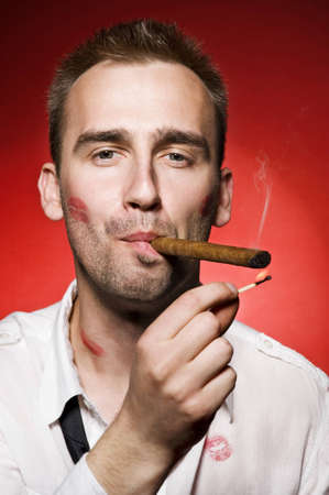 lipstick kiss: portrait of young confident man smoking cigar