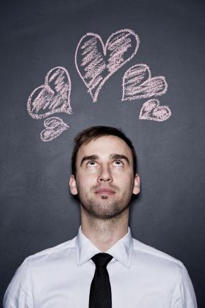 adore: young man and chalk drawn hearts, blackboard wall