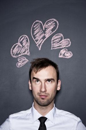 young man and chalk drawn hearts, blackboard wall