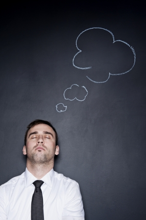 sleeping businessman with a thought cloud on the blackboard wall behind him