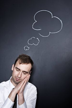 sleeping businessman with a thought cloud on the blackboard wall behind him  Standard-Bild