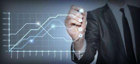 Businessman draws a graph of growth