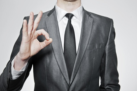 successfull businessman making ok sign, over white background