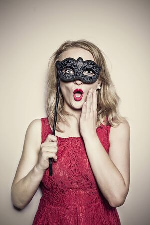 girl in a red dress with a carnival mask