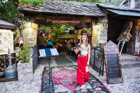 arabian food: Mostar Bosnia - 29 May 2015: A lady is welcoming guests into one Arabian food restaurant
