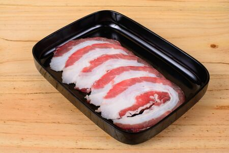 Raw beef brisket in black tray on wooden background.