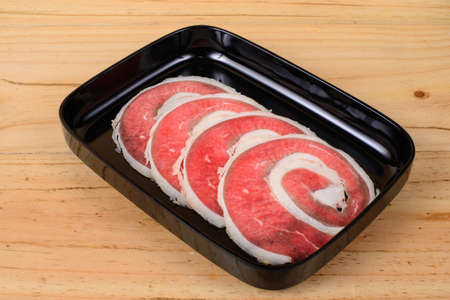 flank: Raw beef flank in black tray on wooden background.