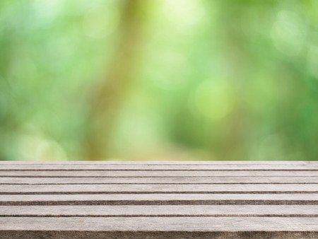 forest products: Wooden board empty table in front of blurred background. Perspective brown wood over blur trees in forest - can be used for display or montage your products. spring season. vintage filtered image. Stock Photo