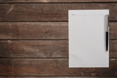 writing paper: Blank notepad with pen on office wooden table.