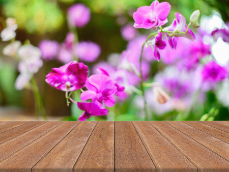 forest products: Wooden board empty table in front of blurred background. Perspective brown wood over blur flower in forest - can be used for display or montage your products. spring season. vintage filtered image.