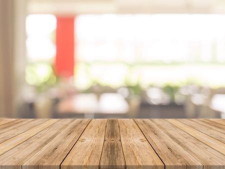 bokeh: Wooden board empty table in front of blurred background. Perspective brown wood over blur in coffee shop - can be used for display or montage your products.Mock up your products.Vintage filter. Stock Photo