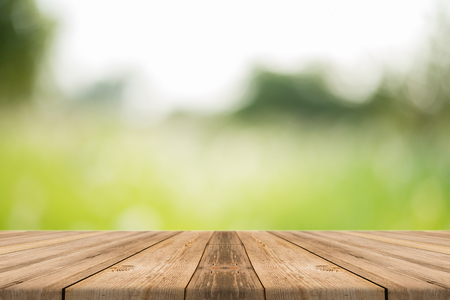 tablero de mesa vacía de madera delante de fondo borroso. Perspectiva de madera marrón sobre los árboles de la falta de definición en el bosque - se puede utilizar para la exhibición o montaje o se burlan de seguridad de sus productos. tus productos. temporada de primavera. Foto de archivo