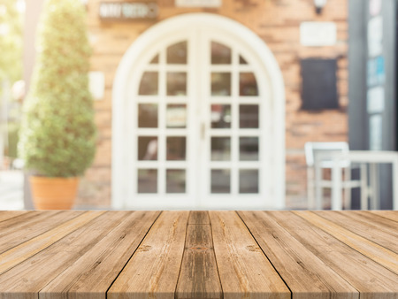 Wooden board empty table in front of blurred background. Perspective brown wood over blur in coffee shop - can be used for display or montage your products.Mock up for display product.Vintage filter. Stock Photo - 50780433