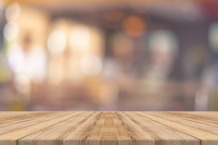 Wooden board empty table in front of blurred background. Perspective brown wood over blur in restaurant - can be used for display or montage your products.Mock up for display of product. Foto de archivo