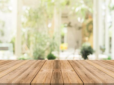 tablero de mesa vacía de madera delante de fondo borroso. Perspectiva de madera marrón sobre la falta de definición en la cafetería - se puede utilizar para la visualización o Montage su products.Mock para la exhibición de productos. Foto de archivo